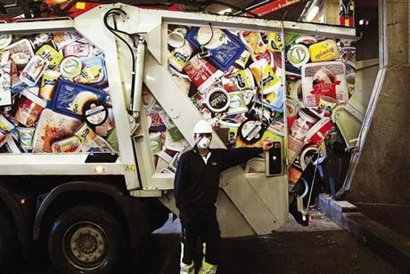 Man with mouth protection in front of garbage truck